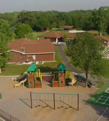 An aerial view of Peterson Park, including the playground complex, trees, and buildings.